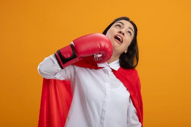 Pijnlijke jonge supervrouw die dooshandschoenen draagt die zich in kin raken die omhoog geïsoleerd op oranje muur kijken