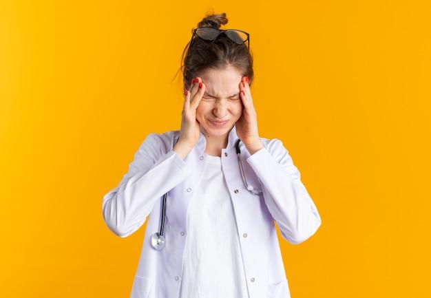 Pijnlijke jonge vrouw in doktersuniform met stethoscoop die haar hoofd vasthoudt