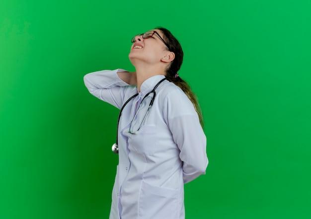 Pijnlijke jonge vrouwelijke arts die een medische mantel en een stethoscoop en een bril draagt die zich in profielweergave bevindt die de handen achter de nek en achter de rug zet geïsoleerd op groene muur met kopie ruimte
