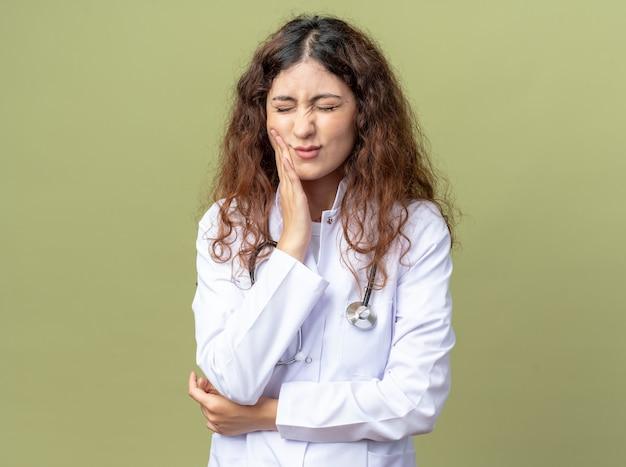 Pijnlijke jonge vrouwelijke arts die medische mantel en stethoscoop draagt en hand op de wang houdt die lijdt aan kiespijn met gesloten ogen geïsoleerd op olijfgroene muur met kopieerruimte