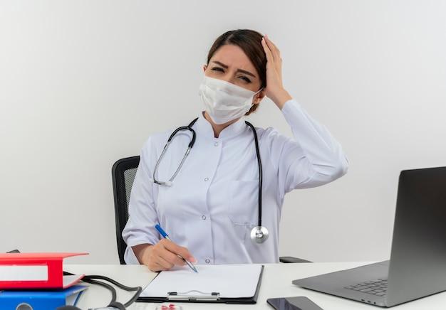 Pijnlijke jonge vrouwelijke arts die medische mantel en stethoscoop en masker draagt ?? die aan bureau zit met medische hulpmiddelen en laptop die hand op hoofd zet die op witte muur wordt geïsoleerd