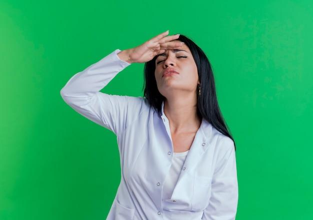 Pijnlijke jonge vrouwelijke arts dragen medische gewaad hand zetten voorhoofd lijden aan hoofdpijn met gesloten ogen geïsoleerd op groene muur met kopie ruimte