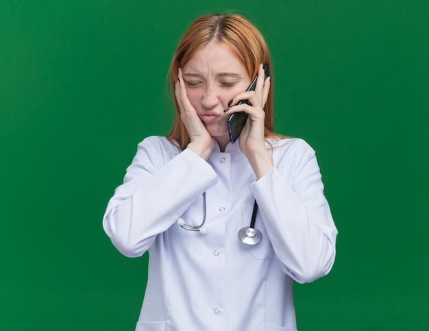 Pijnlijke jonge vrouwelijke gemberdokter met een medisch gewaad en een stethoscoop die aan de telefoon praat en de hand op de wang houdt met gesloten ogen met kiespijn