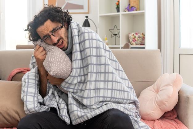 Pijnlijke jonge zieke blanke man met optische bril gewikkeld in plaid met sjaal om zijn nek knuffelend kussen zittend op de bank in de woonkamer