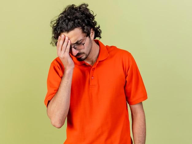 Pijnlijke jonge zieke man met bril hand op het hoofd zetten met gesloten ogen geïsoleerd op olijfgroene muur met kopie ruimte