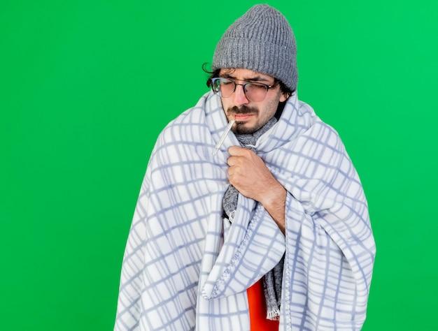 Pijnlijke jonge zieke man met bril, muts en sjaal gewikkeld in geruite thermometer in de mond grijpen plaid met gesloten ogen geïsoleerd op groene muur