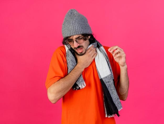 Pijnlijke jonge zieke man met bril, muts en sjaal met keel houden hand in de lucht met gesloten ogen geïsoleerd op roze muur