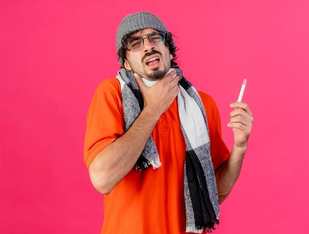 Pijnlijke jonge zieke man met bril, muts en sjaal met thermometer aanraken van keel met gesloten ogen geïsoleerd op roze muur met kopie ruimte