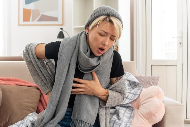 Pijnlijke jonge zieke slavische vrouw met sjaal om haar nek met een wintermuts die hand op haar borst en op haar rug zit zittend op de bank in de woonkamer