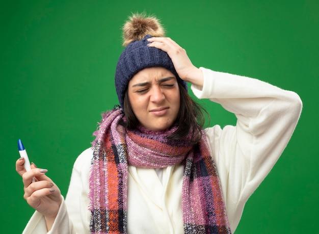 Pijnlijke jonge zieke vrouw die de muts en de sjaal van de gewaadwinter draagt ?? die thermometer houdt die hand op hoofd met gesloten ogen houdt die op groene muur wordt geïsoleerd