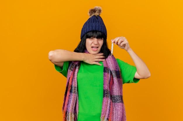 Pijnlijke jonge zieke vrouw die de winterhoed en sjaal draagt ?? die en thermometer bekijkt die hand op keel houdt die op oranje muur wordt geïsoleerd