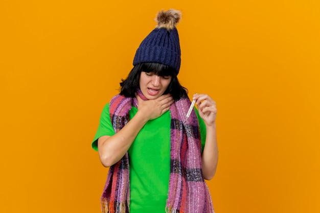 Pijnlijke jonge zieke vrouw die de winterhoed en sjaal draagt die thermometer houdt die hand op keel met gesloten ogen houdt die op oranje muur wordt geïsoleerd
