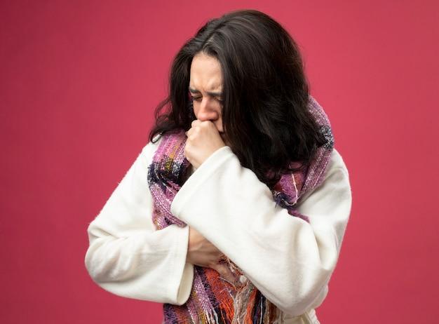Pijnlijke jonge zieke vrouw die een gewaad en een sjaal draagt die hand op de borst en vuist op de mond houdt, hoestend met gesloten ogen geïsoleerd op roze muur