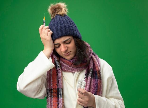 Pijnlijke jonge zieke vrouw die een gewaad, wintermuts en sjaal draagt die spuit en een pak tabletten houdt die de hand op het hoofd houden met gesloten ogen geïsoleerd op groene muur
