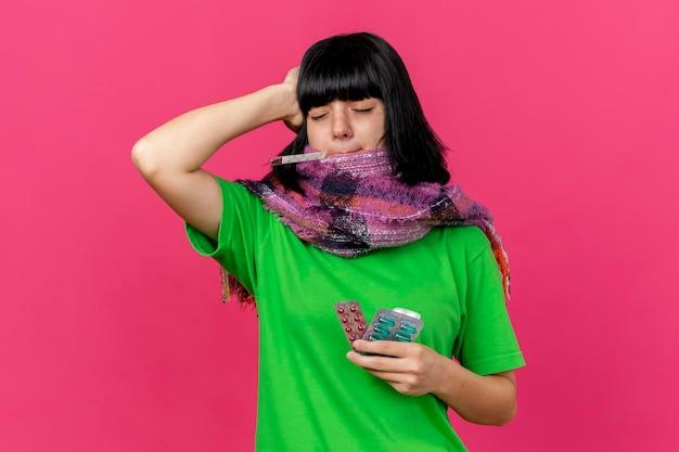 Pijnlijke jonge zieke vrouw die sjaal draagt die thermometer in mond en medische pillen houdt die hand op hoofd houdt met gesloten ogen geïsoleerd op roze muur met exemplaarruimte