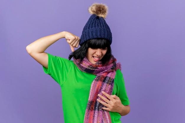 Pijnlijke jonge zieke vrouw dragen winter hoed en sjaal hand op buik en vuist in de lucht houden met gesloten ogen geïsoleerd op paarse muur met kopie ruimte