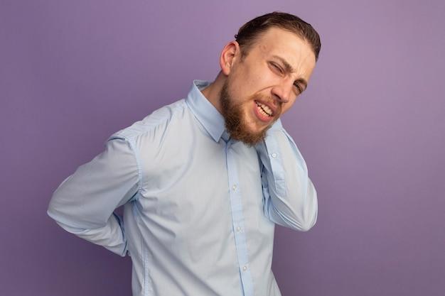 Pijnlijke knappe blonde man houdt rug en nek achter geïsoleerd op paarse muur