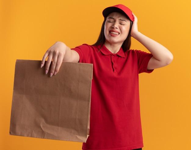Pijnlijke, mooie bezorger in uniform legt hand op het hoofd en houdt een papieren pakket geïsoleerd op een oranje muur met kopieerruimte