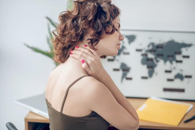 Pijnlijke nek. vrouw tocuhing haar pijnlijke nek tijdens het rusten na een zware werkdag