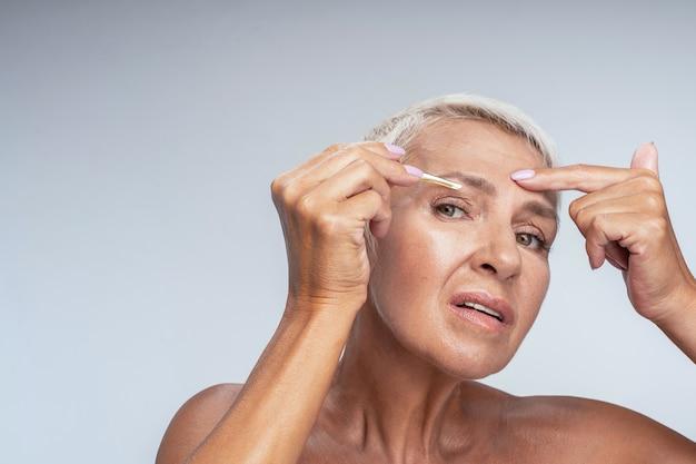 Pijnlijke procedure. rijpe vrouw die haar wenkbrauwen knijpt, staande geïsoleerd op een witte achtergrond