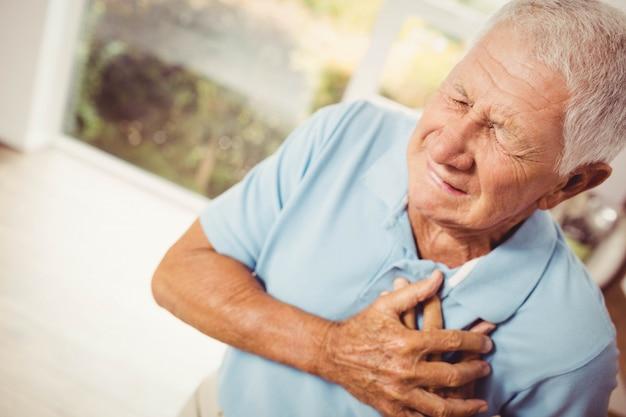 Pijnlijke senior man met pijn op het hart thuis