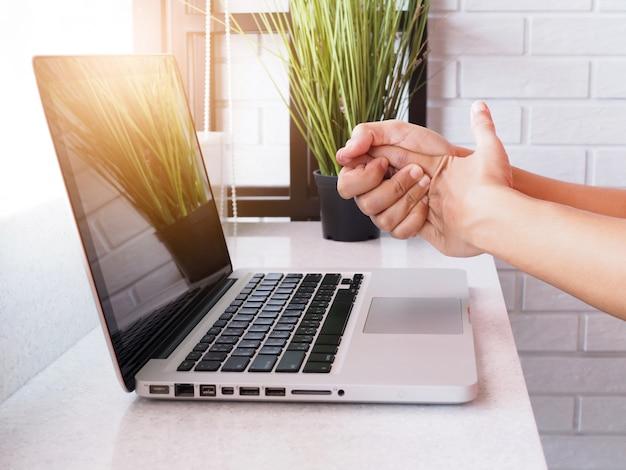Pijnlijke vingers, handpalm en handpijn door het werken met een laptopcomputer, ontsteking van zenuwen en gewrichten, symptoom van reumatoïde artritis of kantoorsyndroom.