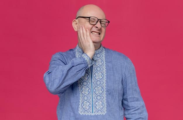 Pijnlijke volwassen man in blauw shirt met een bril die zijn hand op zijn gezicht legt