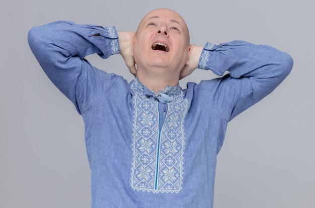 Pijnlijke volwassen slavische man in blauw shirt die handen op zijn hoofd legt en omhoog kijkt