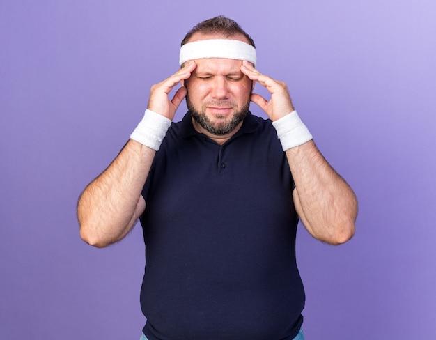 Pijnlijke volwassen slavische sportieve man met hoofdband en polsbandjes die handen op het voorhoofd zetten geïsoleerd op paarse muur met kopieerruimte