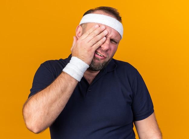 Pijnlijke volwassen slavische sportieve man met hoofdband en polsbandjes legt hand op zijn oog geïsoleerd op oranje muur met kopieerruimte