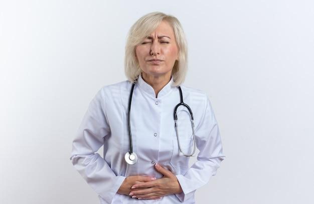 Pijnlijke volwassen slavische vrouwelijke arts in medische mantel met stethoscoop die haar buik vasthoudt op een witte achtergrond met kopieerruimte