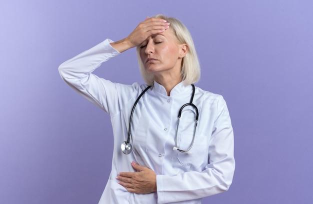 Pijnlijke volwassen vrouwelijke arts in medische mantel met stethoscoop hand op voorhoofd en buik geïsoleerd op paarse muur met kopieerruimte