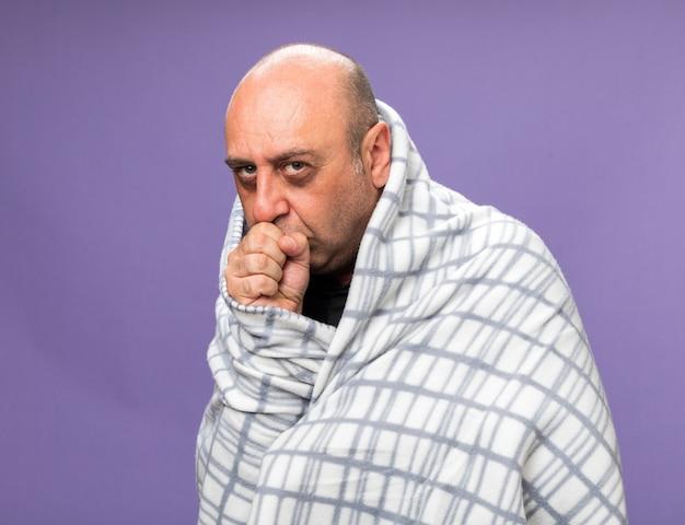 Pijnlijke volwassen zieke blanke man gewikkeld in plaid hoesten geïsoleerd op paarse muur met kopieerruimte