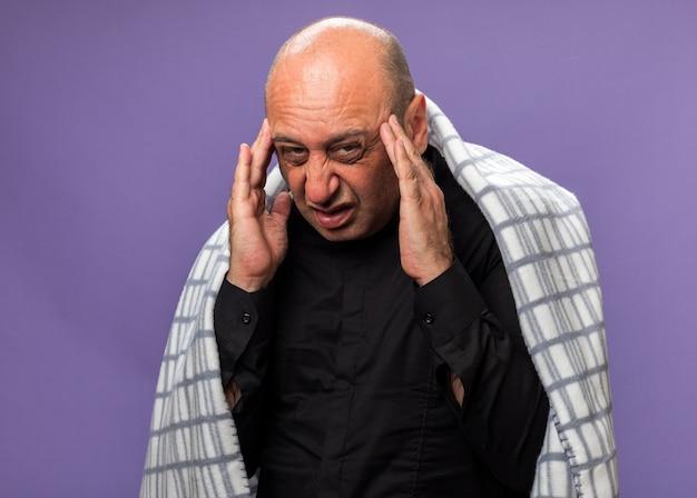 Pijnlijke volwassen zieke blanke man gewikkeld in plaid temperatuur meten met thermometer en hoofd houden geïsoleerd op paarse muur met kopie ruimte