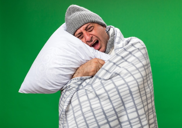 Pijnlijke volwassen zieke blanke man met sjaal om nek dragen winter hoed gewikkeld in plaid vasthouden en hoofd op kussen geïsoleerd op groene muur met kopie ruimte