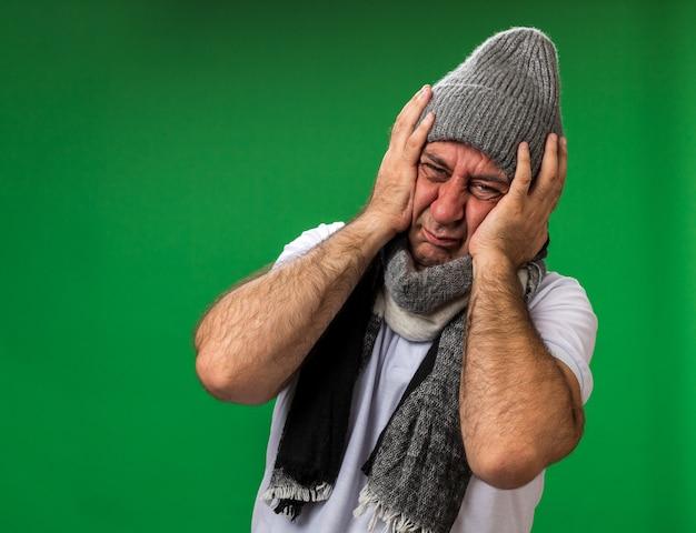 Pijnlijke volwassen zieke blanke man met sjaal om nek dragen winter hoed hoofd houden geïsoleerd op groene muur met kopie ruimte