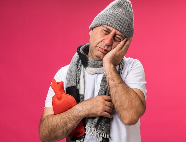 Pijnlijke volwassen zieke blanke man met sjaal om nek met wintermuts legt hand op gezicht en houdt warmwaterkruik geïsoleerd op roze muur met kopieerruimte