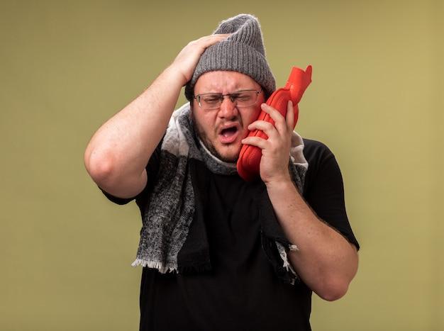 Pijnlijke zieke man van middelbare leeftijd met een wintermuts en sjaal die warmwaterzak op de wang zet en hand op het hoofd zet geïsoleerd op olijfgroene muur