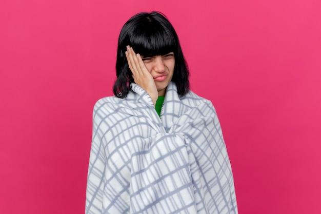 Pijnlijke zwakke jonge zieke blanke meisje gewikkeld in plaid op zoek recht aanraken hoofd geïsoleerd op karmozijnrode muur met kopie ruimte