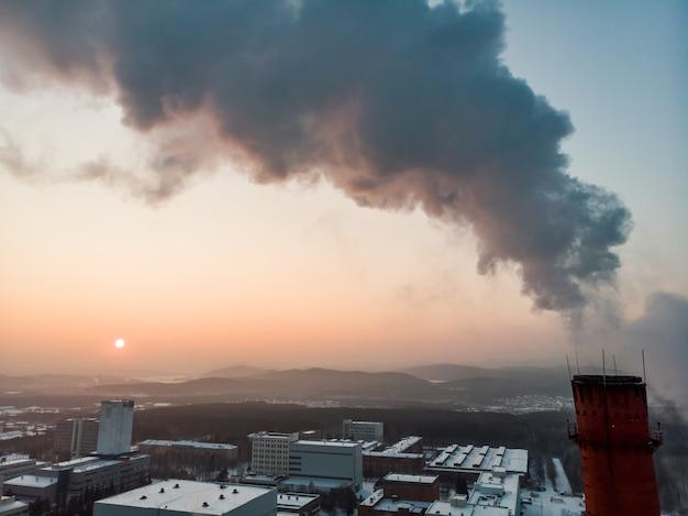 Pijp met rook. warmte-energienetwerk. wkk. warmtekrachtkoppeling, een systeem waarbij stoom geproduceerd in een energiecentrale als bijproduct van elektriciteitsopwekking wordt gebruikt om nabijgelegen gebouwen te verwarmen.
