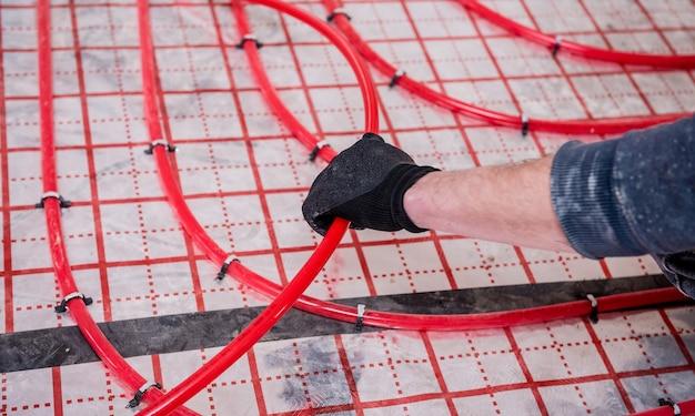 Pijpfitter installeert systeem van vloerverwarming in huis