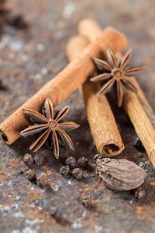 Pijpjes kaneel, anijsplantsterren, kardemom en zwarte peperkorrels op geweven