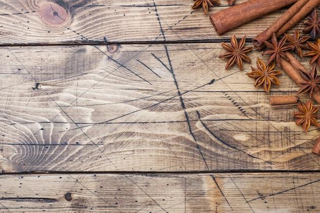 Pijpjes kaneel en anijsplantsterren op houten achtergrond.