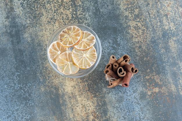 Pijpjes kaneel en gesneden citroenen op marmer.