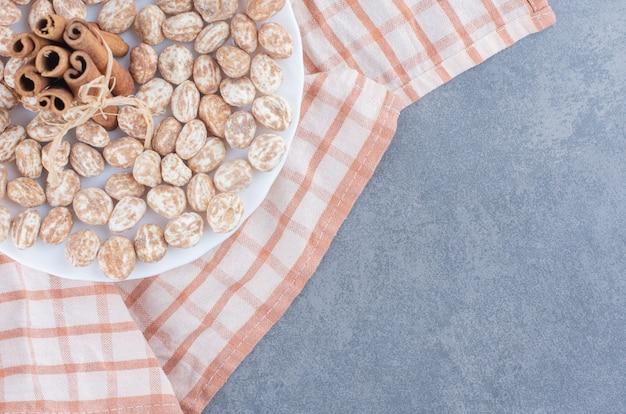 Pijpjes kaneel en koekjes op de handdoek, op de marmeren achtergrond.