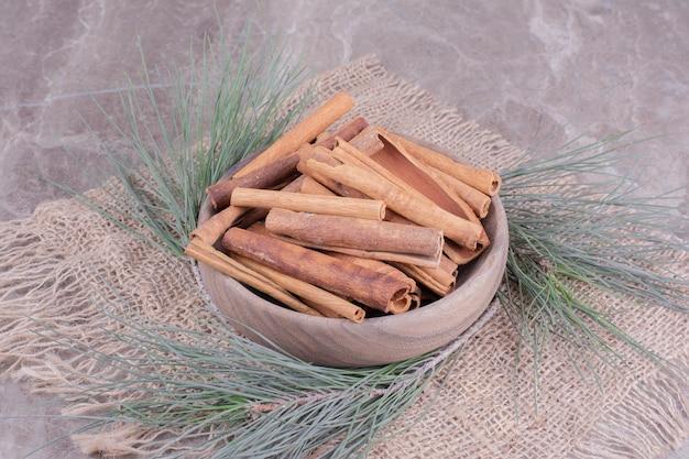 Pijpjes kaneel in een houten kop met rond eikenboomtak