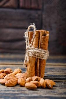 Pijpjes kaneel met amandelen op steentegel en houten