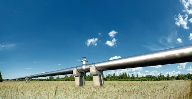 Pijpleiding op straat in het veld, het transport van olie en gas door leidingen. technologie, politiek, grondstoffen, economie. kopieer ruimte. gemengde media.