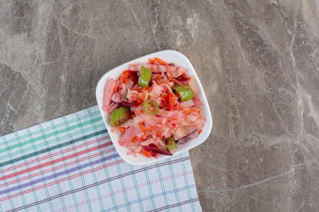 Pikante kom geassorteerde groenten in het zuur op tafellaken op marmer.