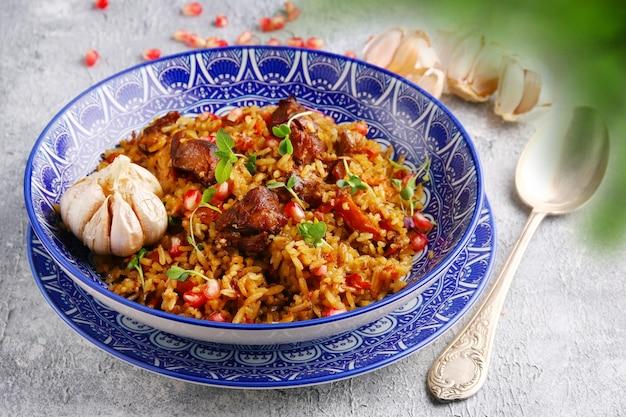 Pilaf en ingrediënten op plaat close-up. nationale oezbeekse pilaf met vlees.